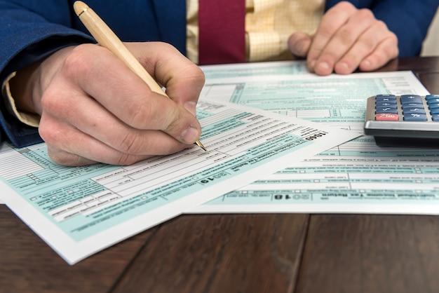 Mężczyzna wypełniający i księgowy dokument finansowy, formularz podatkowy 1040 z kalkulatorem. czas na podatek