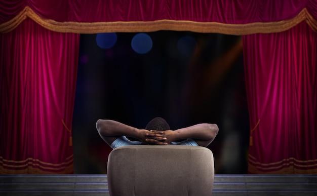 Mężczyzna wypoczywa na fotelu i ogląda przedstawienie w teatrze
