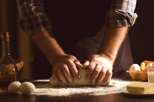 Mężczyzna wyrabia ciasto w kuchni
