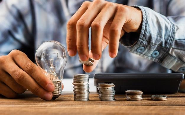 Mężczyzna wyrównuje oszczędzanie monety na stole