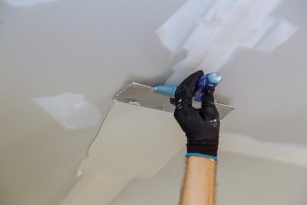Mężczyzna wyrównuje ścianę z szpachelką pracuje z kitu i szpachelki ścianą