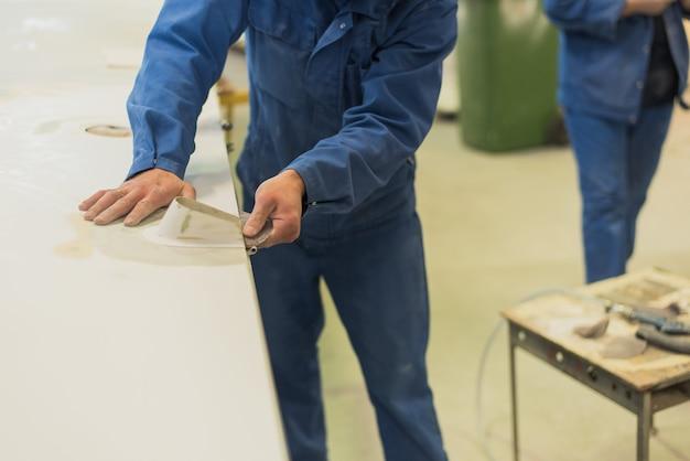 Mężczyzna wyrównuje skrzydło papieru ściernego. pracownik poleruje powierzchnię roboczą