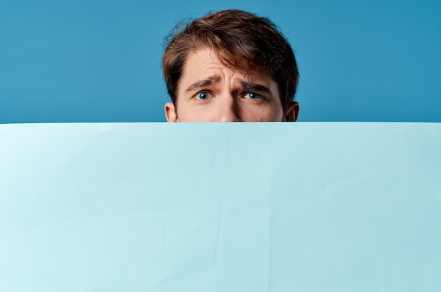 Mężczyzna wystającym zza banera reklamowego z bliska kopiowanie przestrzeni marketingowej