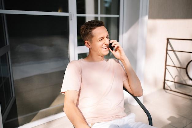 Mężczyzna wysyłający sms-y na telefon komórkowy siedzący na krześle na balkonie