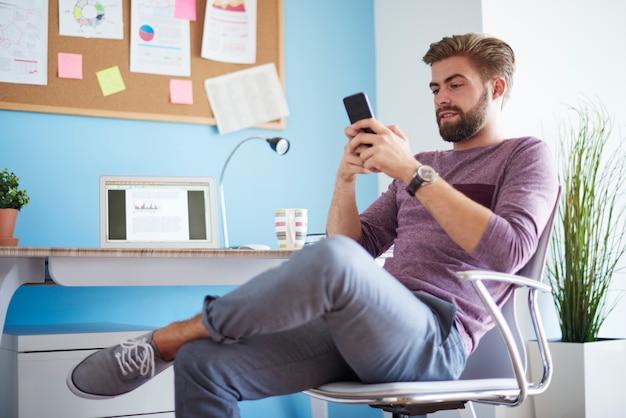 Mężczyzna wysyłający sms-y ze swojego telefonu komórkowego