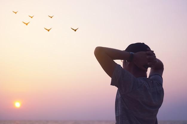 Mężczyzna wzrosta ręki do nieba patrzeje ptaki lata przez metafory wolności pojęcia z zmierzchu niebem i lata plażowym tłem.