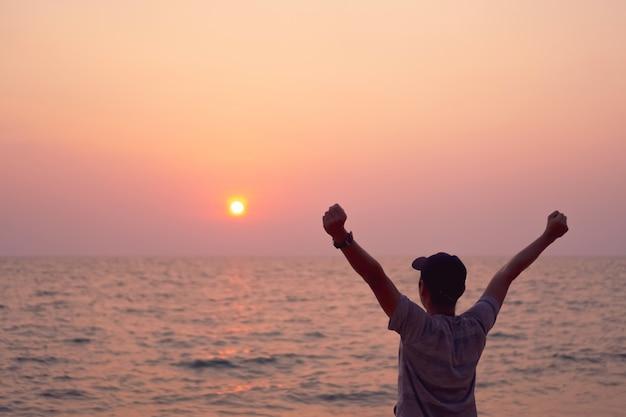 Mężczyzna wzrosta ręki do niebo wolności pojęcia z niebieskiego nieba i lata plażowym tłem.