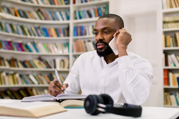 Mężczyzna z afryki student studiujący w bibliotece uczelni, siedzący przy stole, rozmawiający przez telefon i pisający notatki. białe półki z różnymi książkami