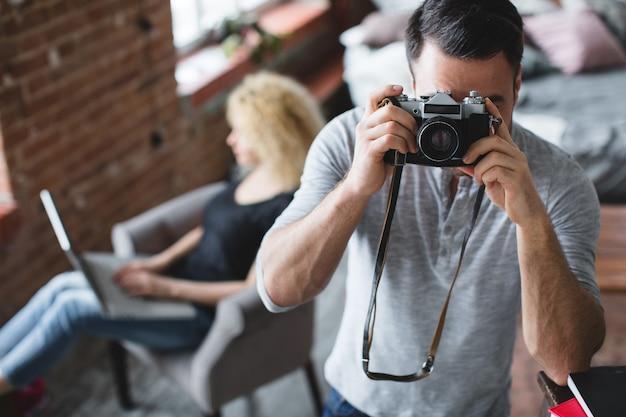Mężczyzna z aparatem fotograficznym z kobietą siedzącą z laptopem