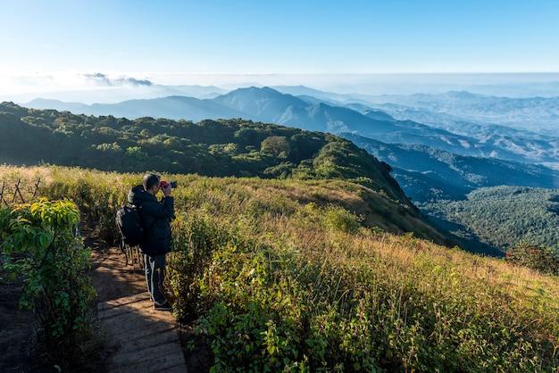 Mężczyzna z aparatem fotografuje viwe w punkcie widokowym kew mae parn doi inthanon chiang mai w tajlandii