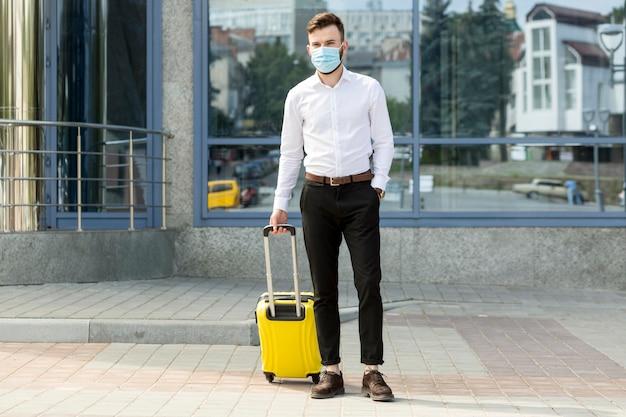 Mężczyzna z bagażem na sobie maskę