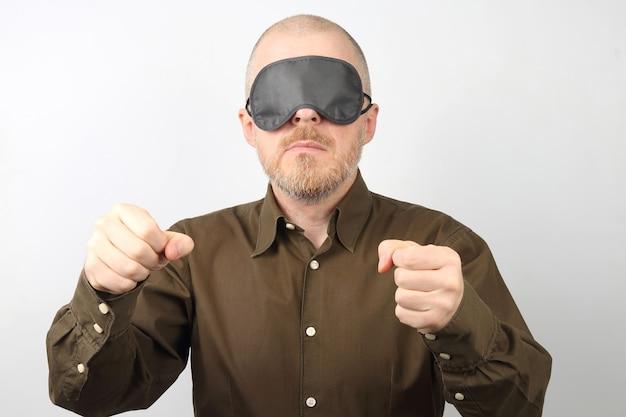 Mężczyzna z bandażem na twarzy do spania z rękami do góry.