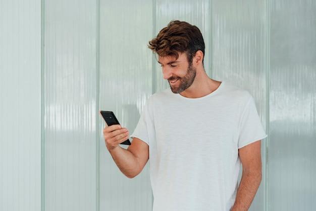 Mężczyzna z białą koszulką trzyma telefon
