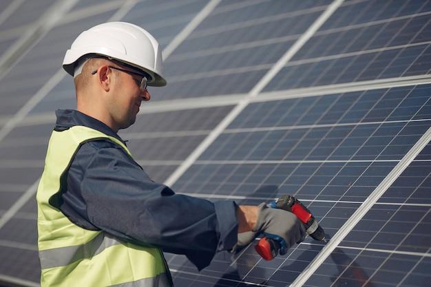 Mężczyzna z białym hełmem blisko panelu słonecznego