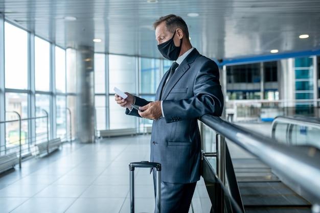 Mężczyzna z biletem i walizką w hali lotniska