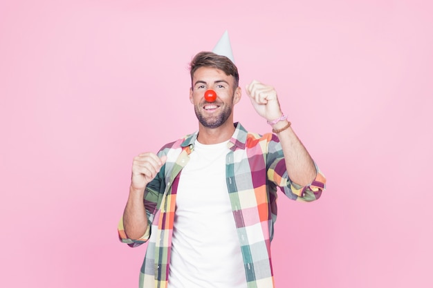 Mężczyzna z błazenu nosa tanem na różowym tle