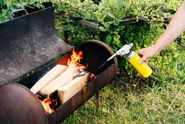 Mężczyzna z bliska trzyma palnik gazowy z balonem i rozpala ogień w grillu z pistoletu na płomienie