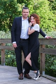 Mężczyzna z bliskiego wschodu w garniturze z żoną w czarnej sukience szczęśliwy mąż i żona