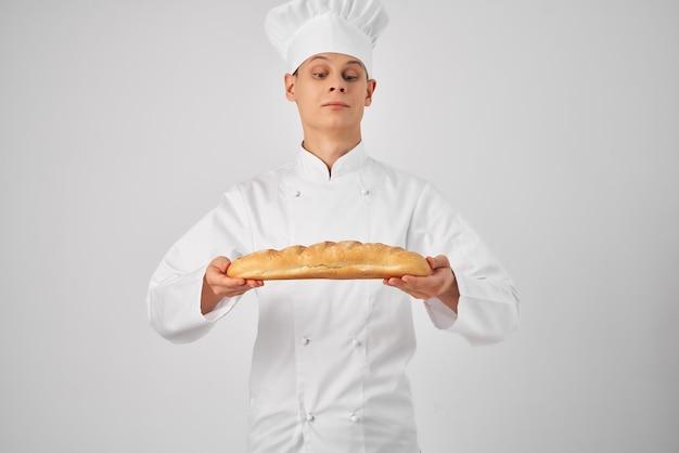Mężczyzna z bochenkiem w rękach w ubraniach kucharzy gotujących jedzenie piekarz