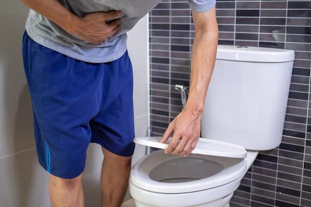 Mężczyzna z bólem brzucha ściska dłonią brzuch.