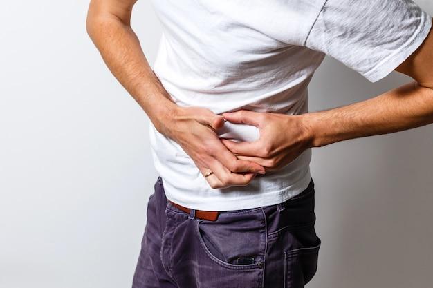 Mężczyzna z bólem brzucha w białej koszulce dyskomfort trawienie niestrawność