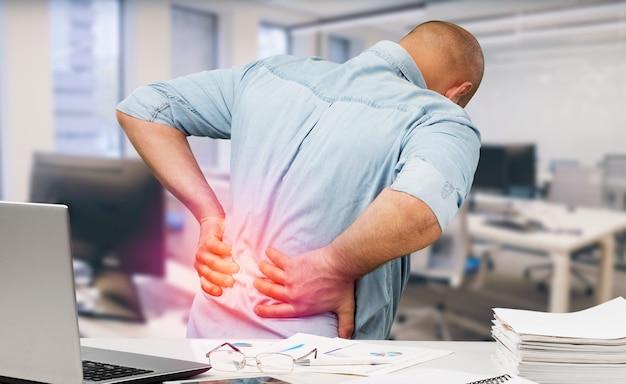 Mężczyzna z bólem pleców w biurze