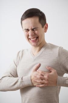 Mężczyzna z bólem serca na białej ścianie