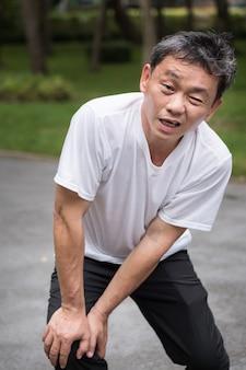 Mężczyzna z bólem stawu kolanowego, zapaleniem stawów azjata w podeszłym wieku lub w średnim wieku