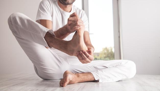 Mężczyzna z bólem stopy w domu