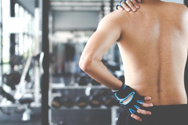Mężczyzna z bólem szyi i pleców, masaż męskiego ciała, ból w ciele mężczyzny na siłowni.