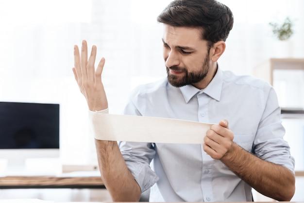 Mężczyzna z bólem w ręku siedzi w białym biurze.