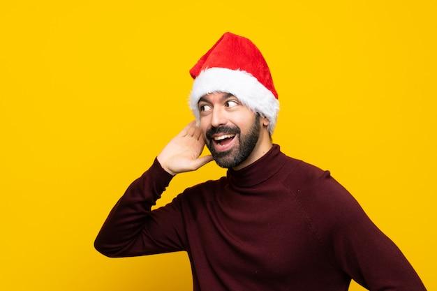 Mężczyzna z boże narodzenie kapeluszem nad odosobnioną kolor żółty ścianą słucha coś stawiając rękę na ucho