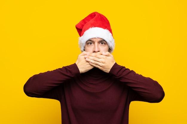 Mężczyzna z boże narodzenie kapeluszem nad odosobnionym kolor żółty ściany nakrywkowym usta z rękami