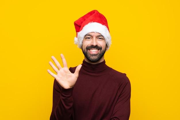 Mężczyzna z bożymi narodzeniami kapeluszowymi nad odosobnioną kolor żółty ścianą liczy pięć z palcami
