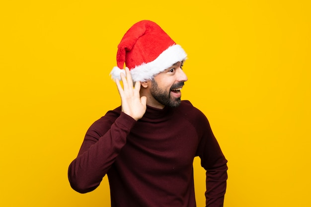 Mężczyzna z bożymi narodzeniami kapeluszowymi nad odosobnioną kolor żółty ścianą słucha coś stawiając rękę na ucho