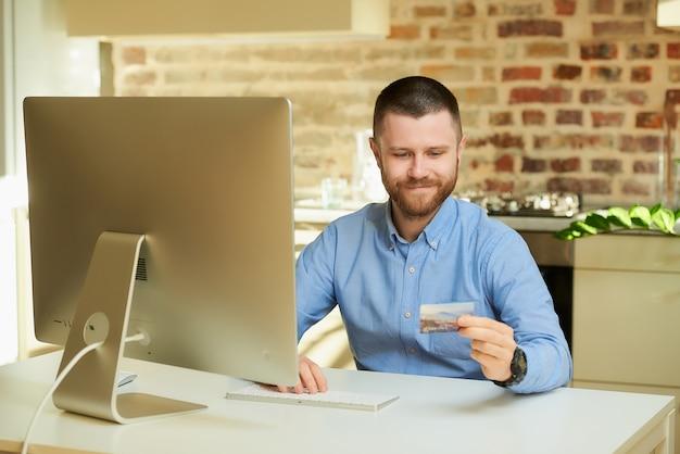 Mężczyzna z brodą chce robić zakupy online i z niecierpliwością spogląda na swoją kartę kredytową w domu
