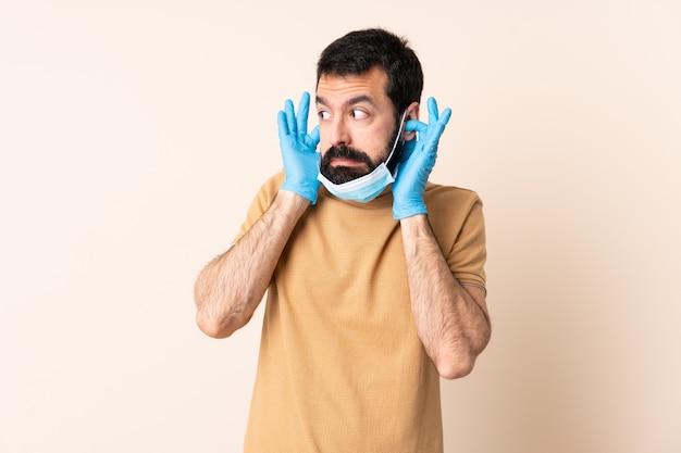 Mężczyzna z brodą chroniąc przed koronawirusem za pomocą maski i rękawiczek na izolowanej ścianie sfrustrowany i zakrywający uszy