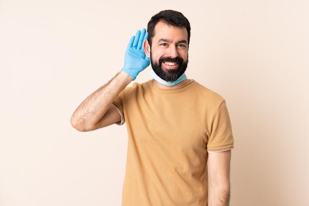 Mężczyzna z brodą chroniącą przed koronawirusem z maską i rękawiczkami na izolowanej ścianie, słuchając czegoś, kładąc rękę na uchu