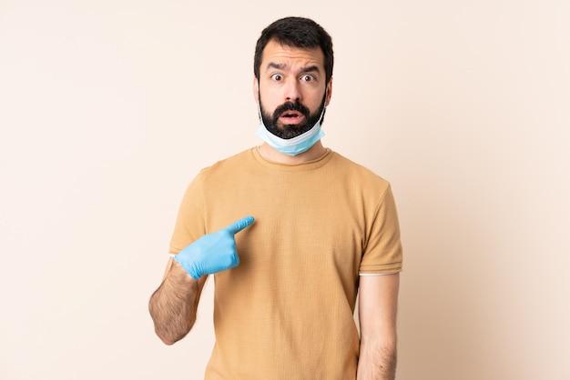 Mężczyzna z brodą chroniącą przed koronawirusem z maską i rękawiczkami na izolowanej ścianie, wskazując na siebie