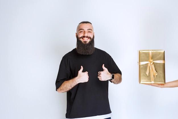 Mężczyzna z brodą czuje się dobrze ze swoim złotym, drogim pudełkiem prezentowym.