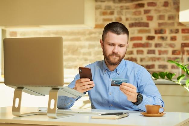 Mężczyzna z brodą czyta informacje z tyłu karty kredytowej i wpisuje je na smartfonie, aby dokonać zakupu online w domu