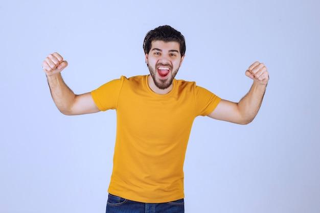 Mężczyzna z brodą demonstruje mięśnie pięści i ramion i czuje się potężny