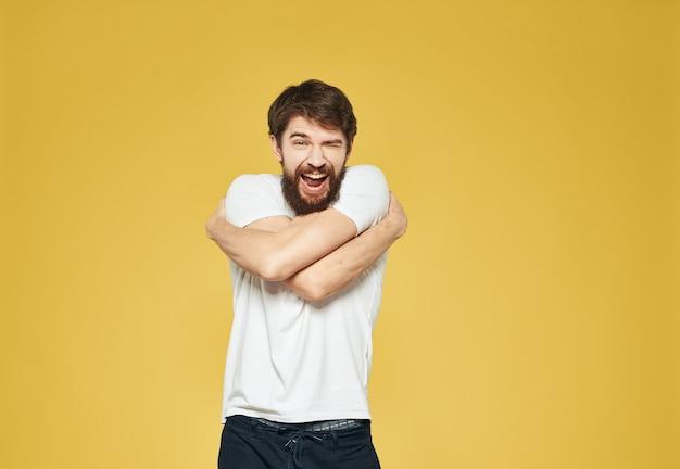 Mężczyzna z brodą gestykuluje rękami na żółtym tle, a ciemne spodnie to model