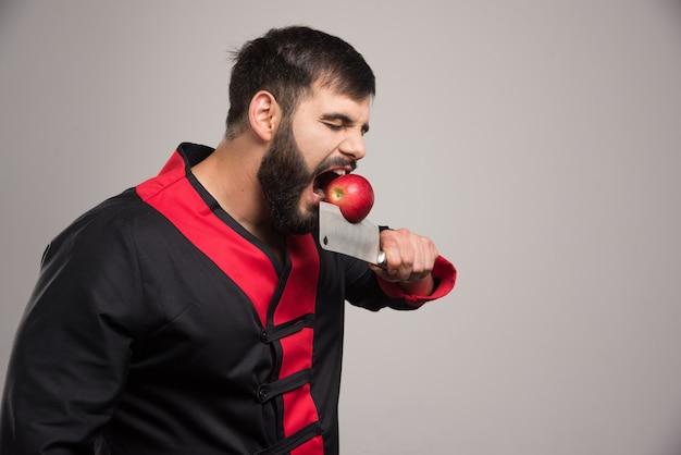Mężczyzna z brodą gryzie czerwone jabłko na nożu.