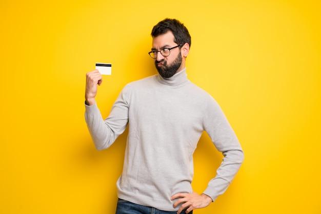 Mężczyzna z brodą i golfem bierze kartę kredytową bez pieniędzy