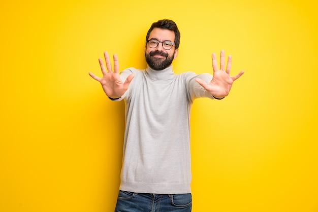 Mężczyzna z brodą i golfem liczący dziesięć palcami