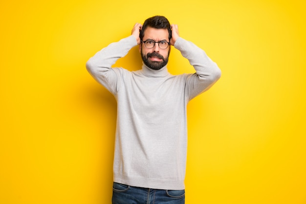 Mężczyzna z brodą i golfem ma ręce na głowie, ponieważ ma migrenę