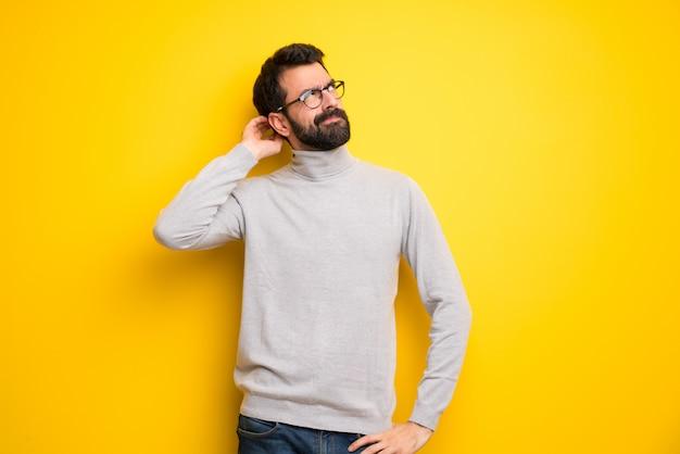 Mężczyzna z brodą i golfem ma wątpliwości podczas drapania głowy
