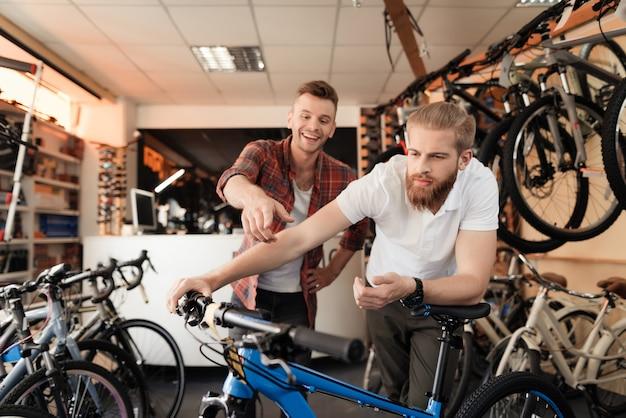 Mężczyzna z brodą i klientem przygląda się uważnie towarom