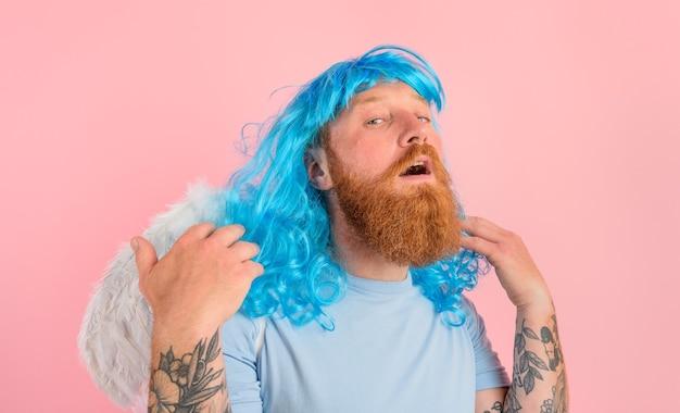 Mężczyzna z brodą i niebieską peruką zachowuje się jak anioł ze skrzydłami